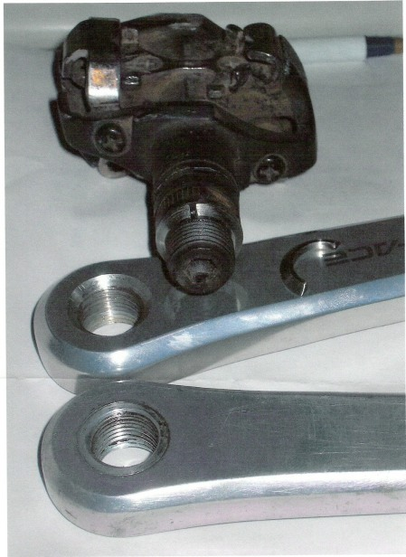 Jobst solution for crank failure at pedal eye. There's a 2-piece washer that fits into the drilled indent. One half is shown on the crank; both halves shown on the pedal thread.
