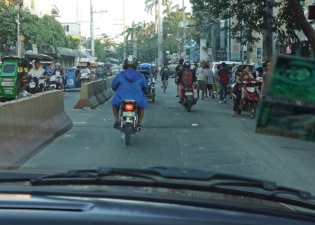 Typical street scene in a Manila suburb. Tricycle motorbikes, motorbikes, cars, bicycles, pedestrians, trucks.